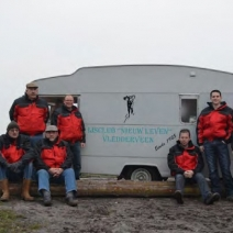 """Leden van het bestuur van de ijsclub """"Nieuw Leven"""" bij hun koek en zopie -caravan"""